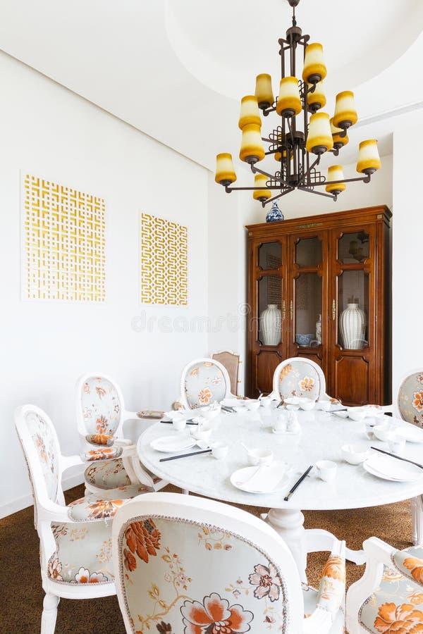 Stanza cinese moderna del ristorante VIP con i fiori su tessuto decorato sulle sedie gabinetto di legno con le porcellane dentro fotografie stock