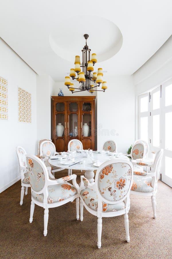 Stanza cinese moderna del ristorante VIP con i fiori su tessuto decorato sulle sedie gabinetto di legno con le porcellane dentro immagini stock