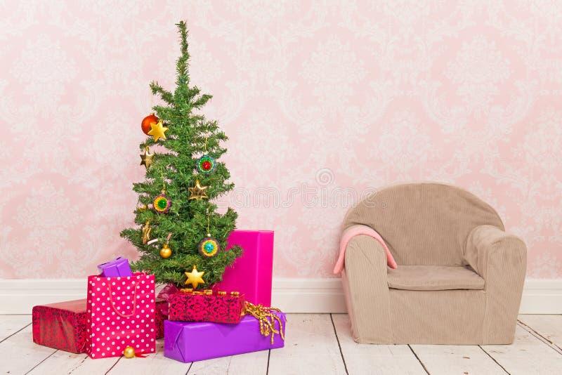 Stanza d'annata con l'albero di Natale, i regali e la sedia immagini stock