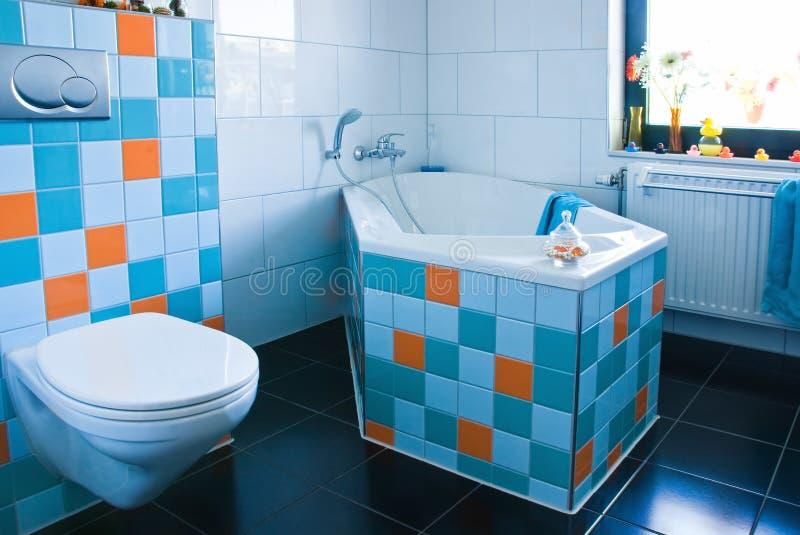 Stanza da bagno bianca e blu variopinta con il pavimento nero fotografia stock