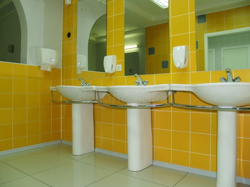 Stanza da bagno o toletta con lle mattonelle gialle, ciotole immagine stock libera da diritti