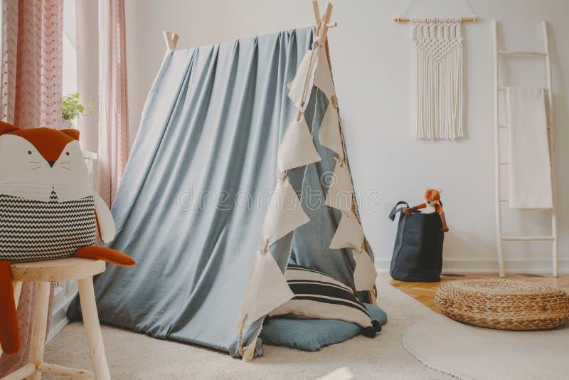 Stanza dei giochi naturale con la tenda scandinava blu, la mobilia di legno ed il macramè fatto a mano sulla parete, foto reale immagini stock libere da diritti