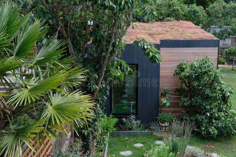 Stanza del giardino, ritirata verde con l'ape amichevole, tetto vivente di sedum in giardino ben rifornito e maturo fotografie stock libere da diritti