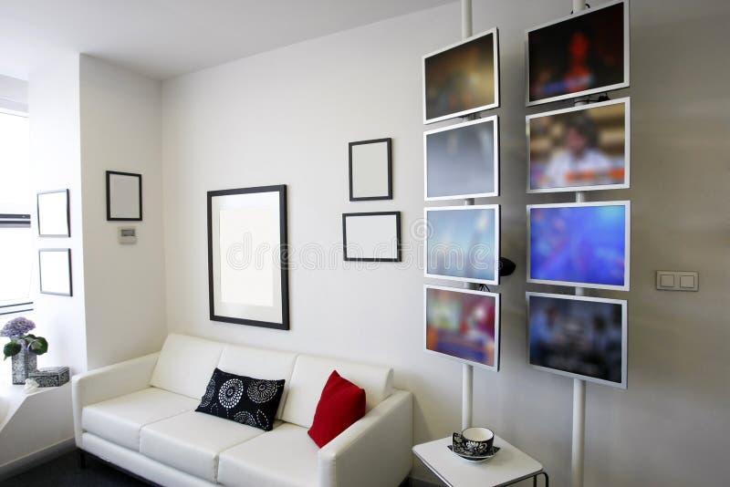 Stanza del salotto con lo strato bianco e le visualizzazioni dell'affissione a cristalli liquidi fotografia stock
