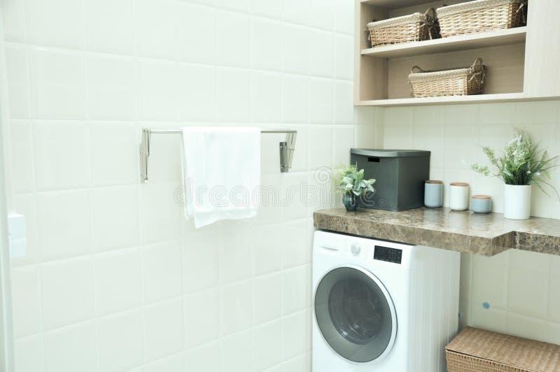 Stanza di lavanderia con la macchina della lavanderia ed il gancio bianchi dell'asciugamano su briciolo immagini stock