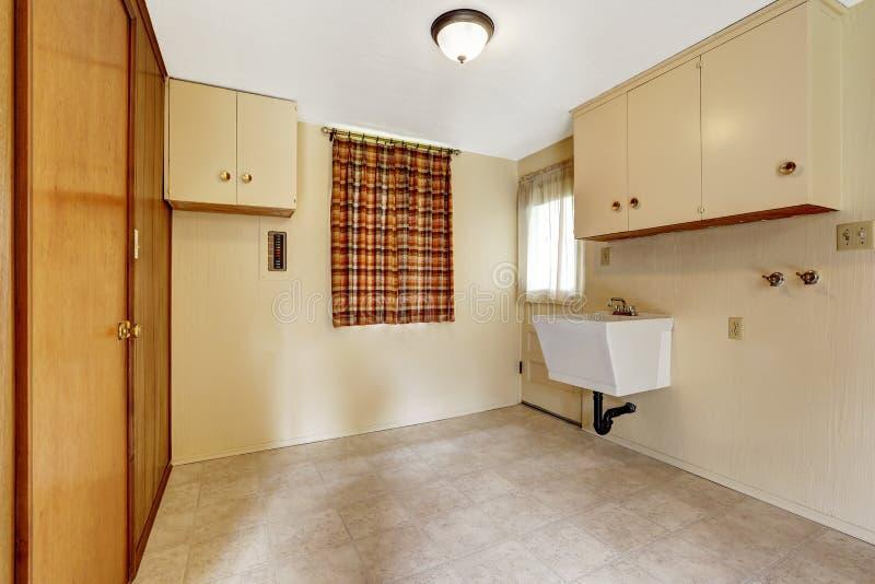 Stanza di lavanderia con le pareti e la pavimentazione in piastrelle beige ammobiliato di gabinetti e di guardaroba incorporato fotografia stock libera da diritti