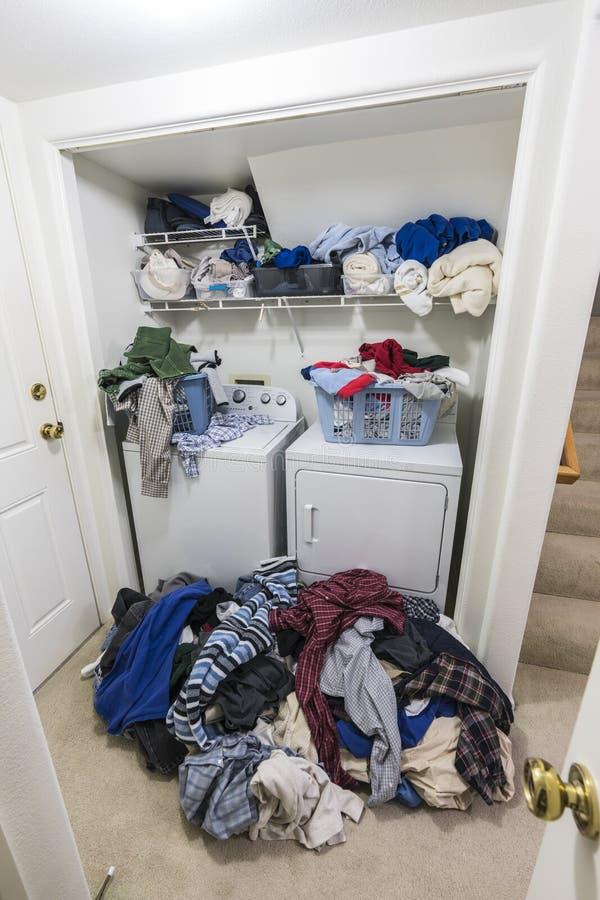 Stanza di lavanderia sudicia con i mucchi della vista di verticale dei vestiti fotografia stock libera da diritti