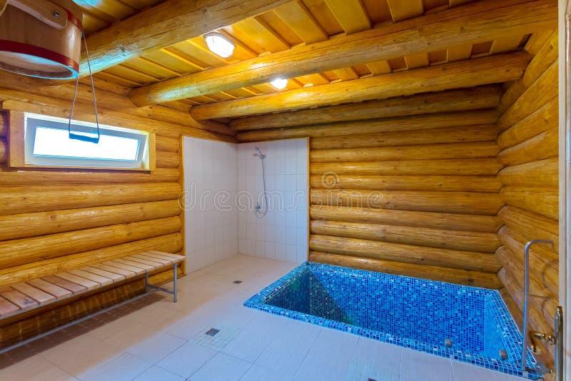 Stanza di legno nel bagno per il raffreddamento di contrapposizione con uno stagno e una doccia blu fotografia stock libera da diritti