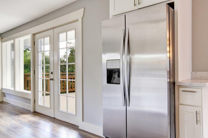 Stanza luminosa della cucina con gli apparecchi e le cime d'acciaio del granito immagini stock