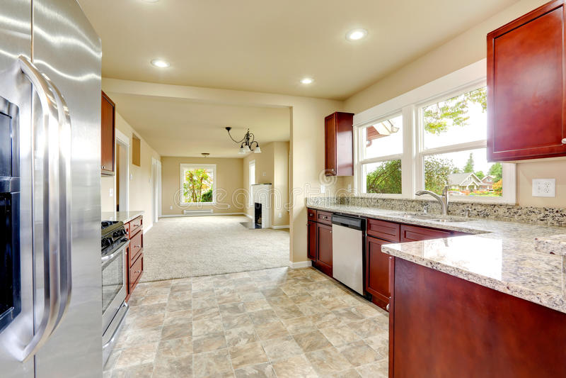 Stanza luminosa della cucina con le cime del granito ed i gabinetti di Borgogna fotografia stock libera da diritti