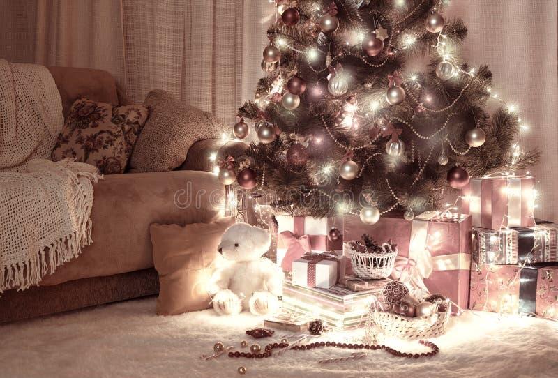 Stanza nello scuro con l'albero di Natale, la decorazione ed i regali illuminati, interno della casa alla notte, marrone-rosso to immagini stock