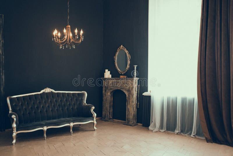 Stanza nera nel castello con una finestra, un candeliere, un sofà e uno specchio e camino fotografia stock