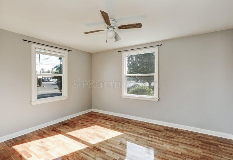 Stanza non ammobiliata soleggiata con il pavimento di legno duro in vecchia casa vuota fotografia stock libera da diritti