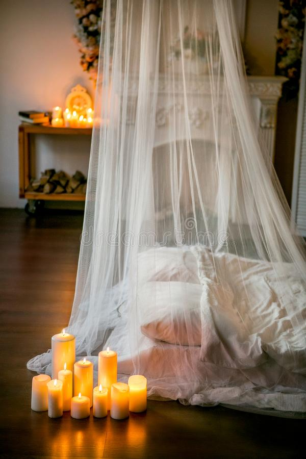 stanza stile sottotetto con un letto, un baldacchino, un camino bianco con una disposizione dei fiori, accesa candele, primo pian fotografie stock
