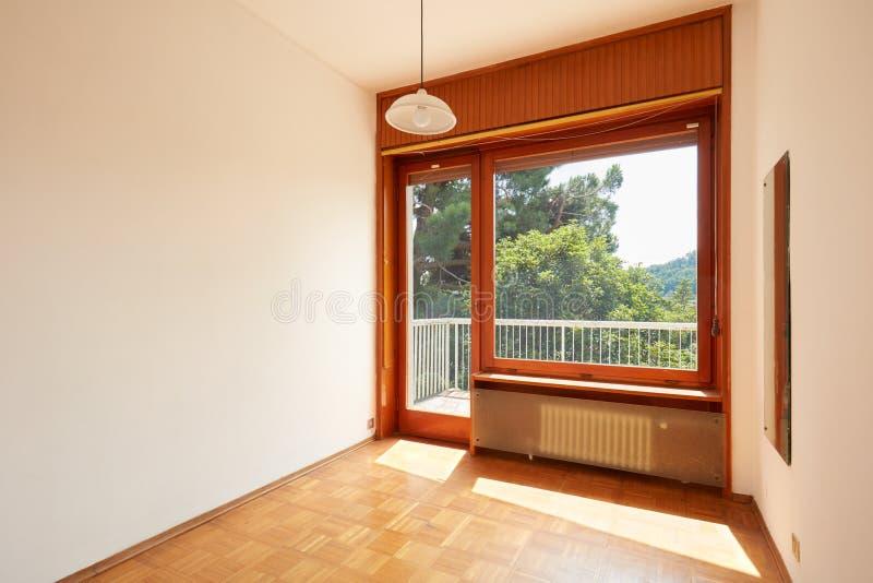 Stanza vuota e soleggiata interna con il pavimento di legno in casa di campagna immagine stock libera da diritti
