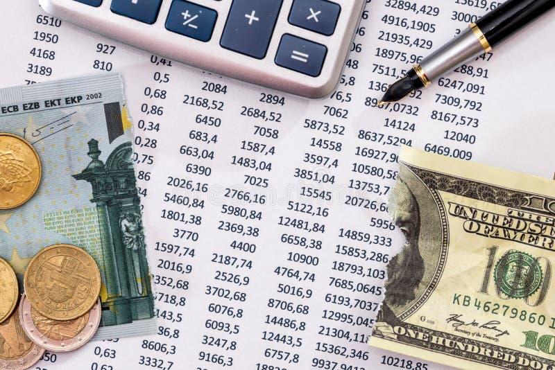 Stanzi il testo con il calcolatore, la penna, lacerato 100 euro ed il dollaro fotografia stock libera da diritti