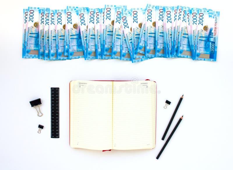 Stanzi la pianificazione, il taccuino, i soldi, il porcellino salvadanaio, vista superiore, sulla tavola fotografie stock