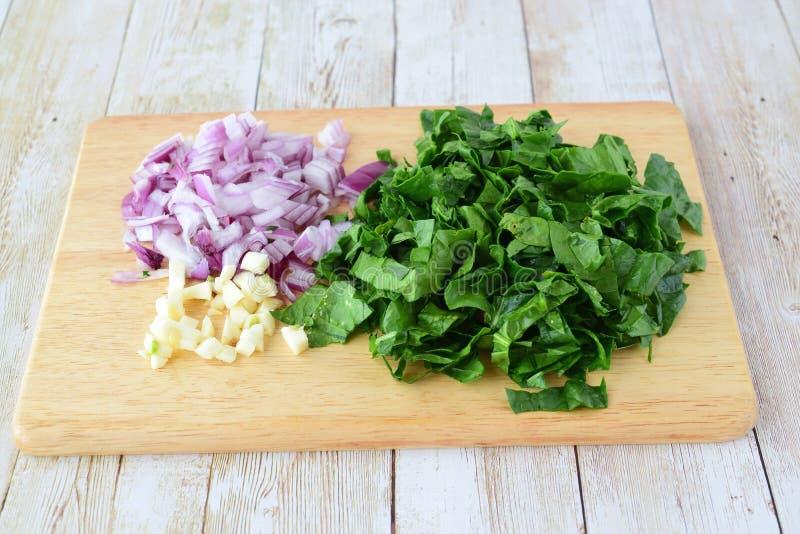 stap voor stap kokend Besnoeiings rode ui, spinazie en knoflook op een houten scherpe raad op een lichte houten achtergrond stock afbeeldingen