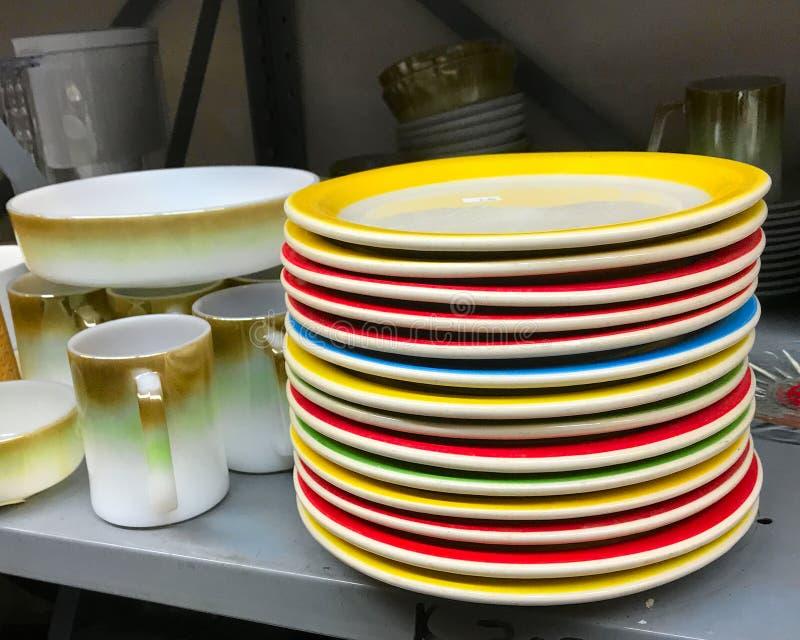 Stapel alte benutzte bunte Teller der großen Teller der Weinlese im Gebrauchtwarengeschäft stockfoto