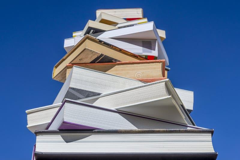 Stapel Bücher der Abstieggröße gegen einen schönen blauen Himmel stockbilder
