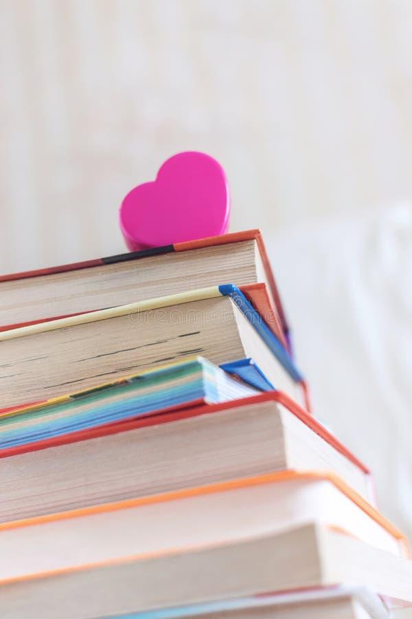 Stapel Bücher und rosa Herz auf dem weißen Bett Ausbildungshintergrund mit Kopienraum, zurück zu Schulkonzept lizenzfreie stockbilder