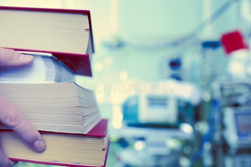 Stapel Bücher in den Händen des Gesundheitsfürsorgers auf dem Hintergrund O lizenzfreies stockbild