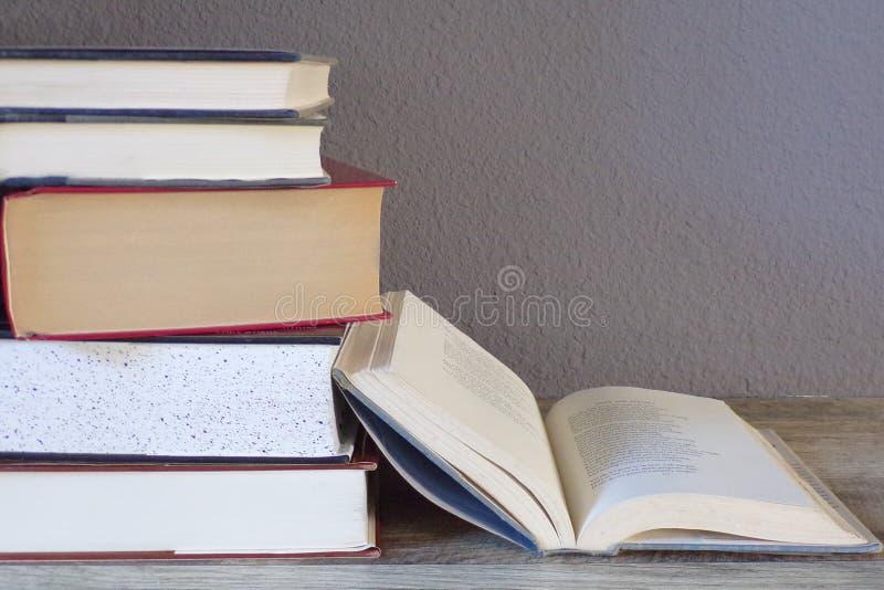 Stapel Bücher, die auf einer Tabelle mit einer offen sitzen lizenzfreie stockbilder