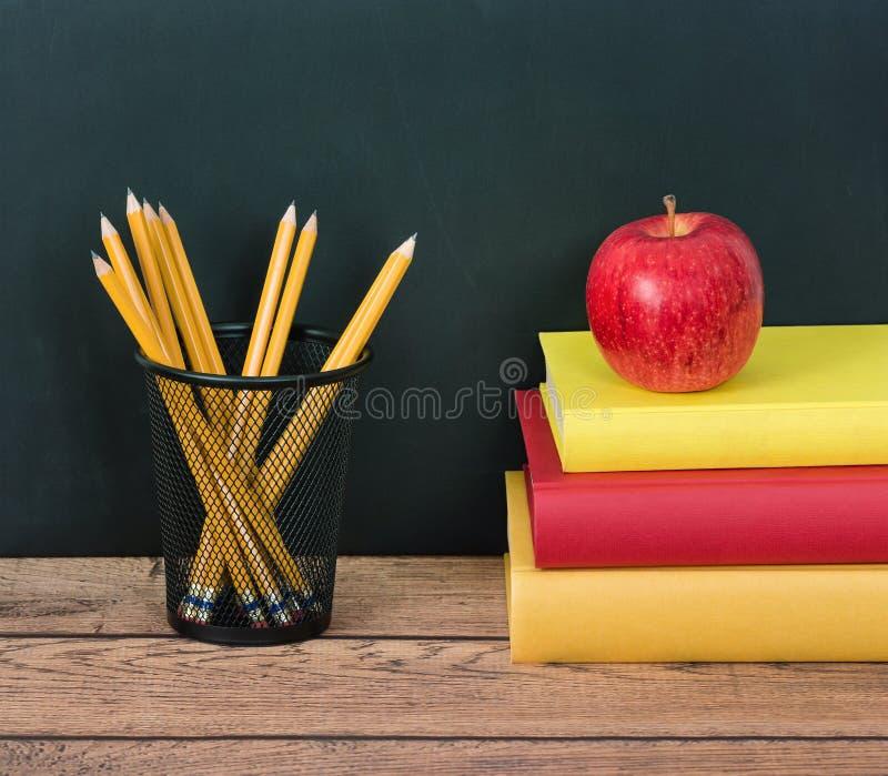 Stapel Bücher mit Apfel und Bleistiften lizenzfreie stockbilder
