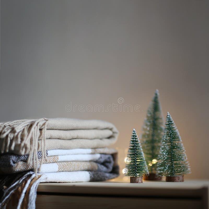 Stapel beige geruite woldekens en twee Kerstbomen op een houten stilleven van de borst Comfortabel winter Huistextiel royalty-vrije stock afbeelding