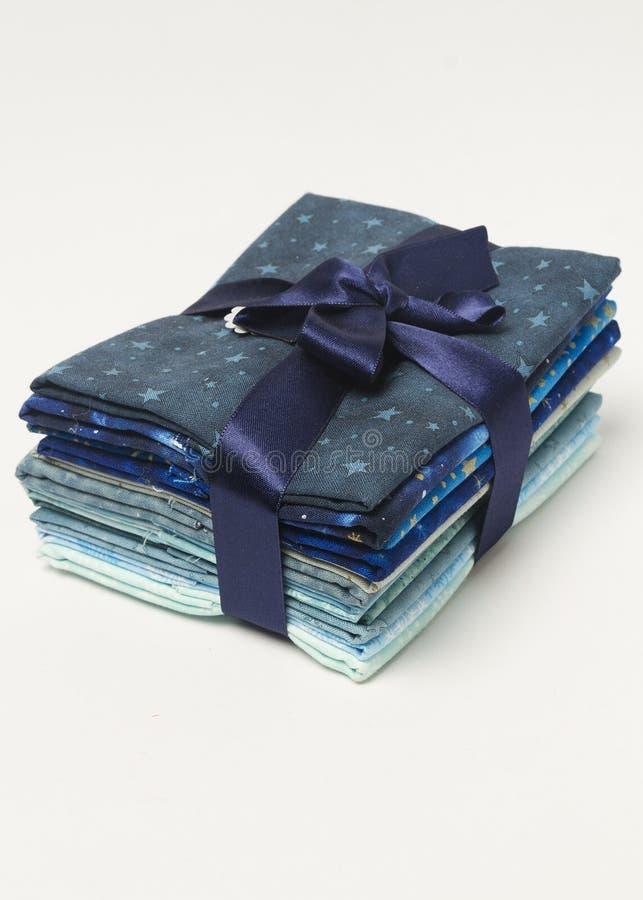 Stapel blauwe schaduwen gevouwen stoffen met gift hierboven lint van stock foto