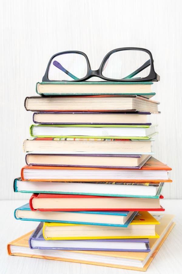 Stapel boeken met oogglazen op bovenkant stock fotografie