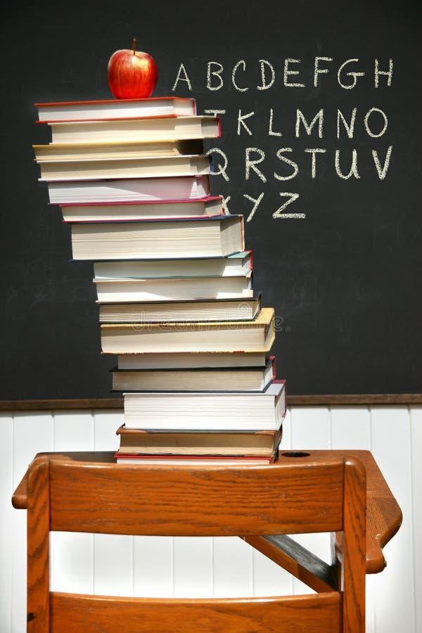 Stapel boeken op een oude schoolbank stock afbeelding