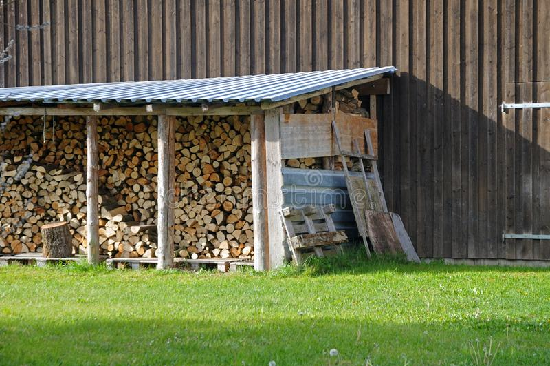 Stapel Brennholz geschützt mit Blechdach lizenzfreies stockfoto