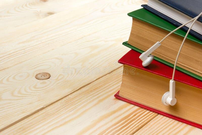 Stapel bunte Bücher auf Holztisch und Kopfhörern Audiobook Konzept lizenzfreie stockfotografie