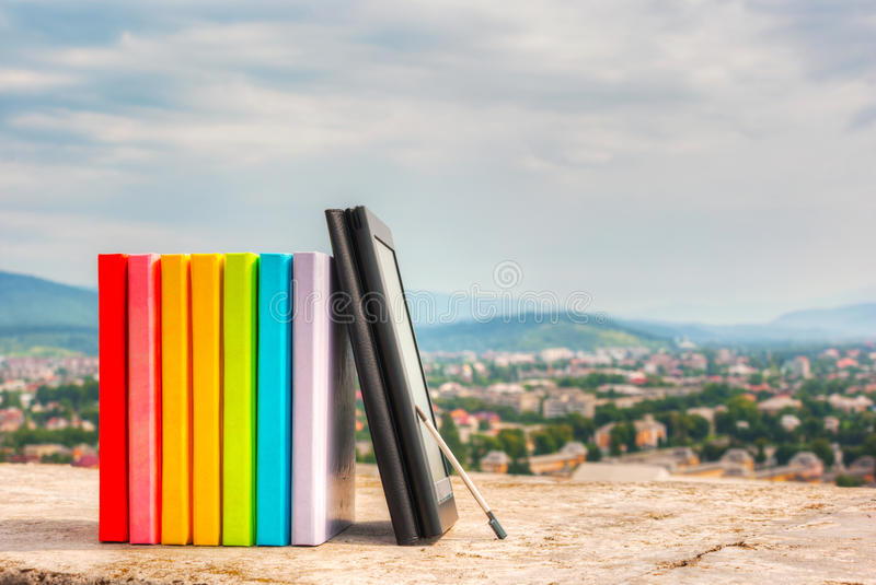 Stapel bunte Bücher mit eBook Leser stockfotos