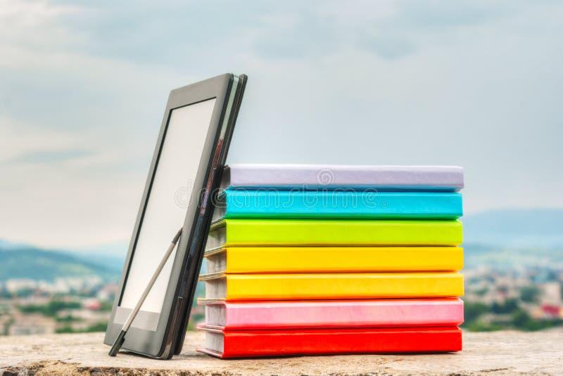 Stapel bunte Bücher mit elektronischem Buchleser stockbilder