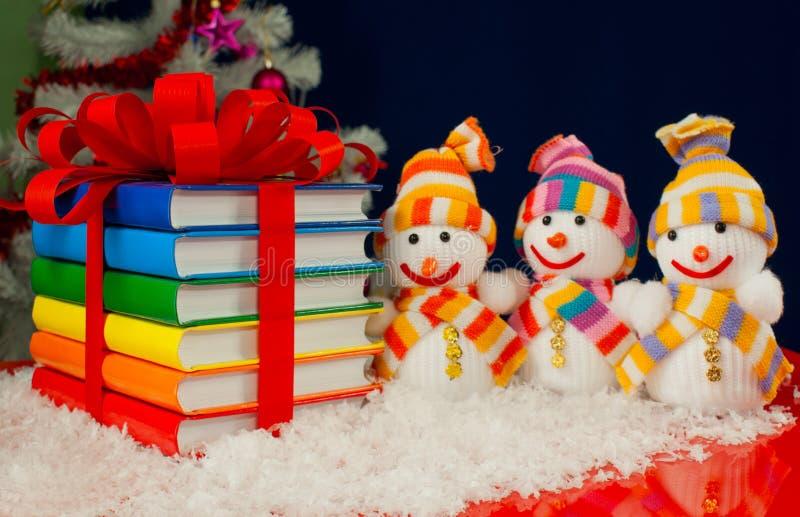 Stapel bunte Bücher und drei Schneemänner stockfotografie