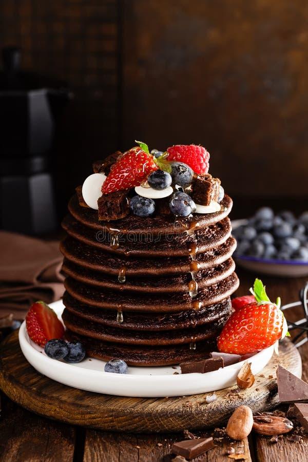 Stapel chocoladepannekoeken met bessen, aardbei, framboos en bosbes stock afbeeldingen