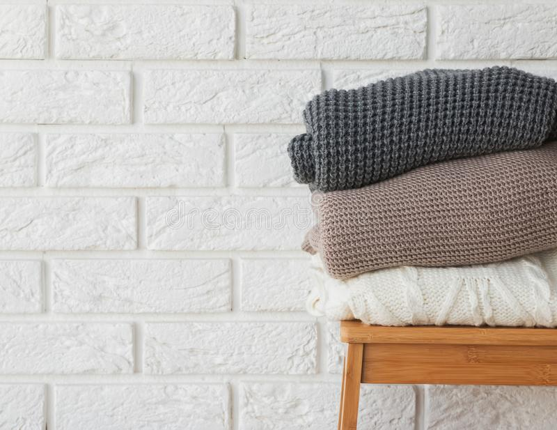 Stapel de wintersweaters op de witte bakstenen muurachtergrond stock foto's