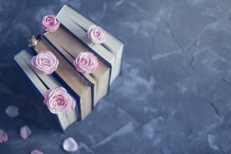 Stapel der alten Bücher mit rosa Rosen auf der Betondecke Geometrische Verzierung auf einem alten Papier stockfotografie