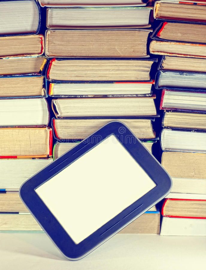 Stapel der bunten Bücher und des elektronischen Buchlesers stockbilder