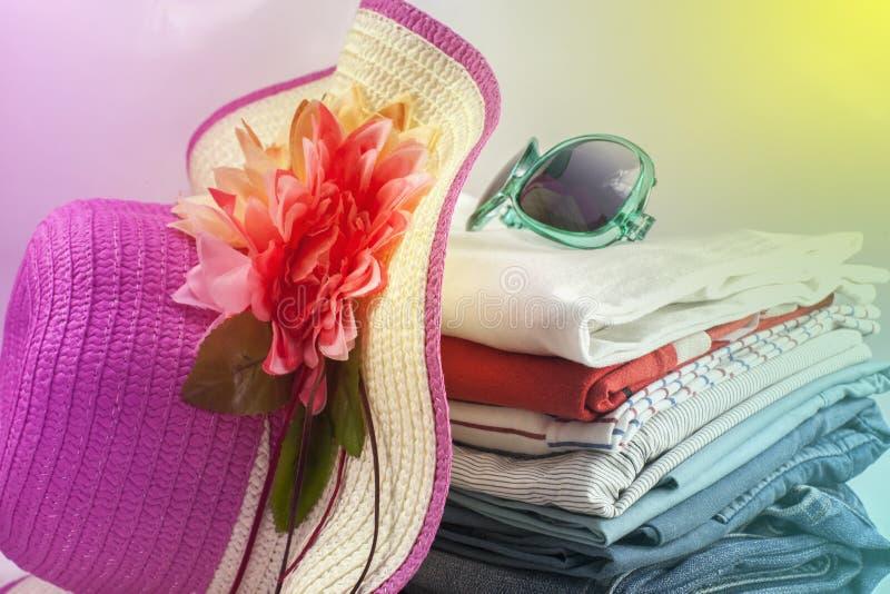 Stapel der bunten Kleidung und des schönen Sommerhutes, süßes beauti lizenzfreies stockbild