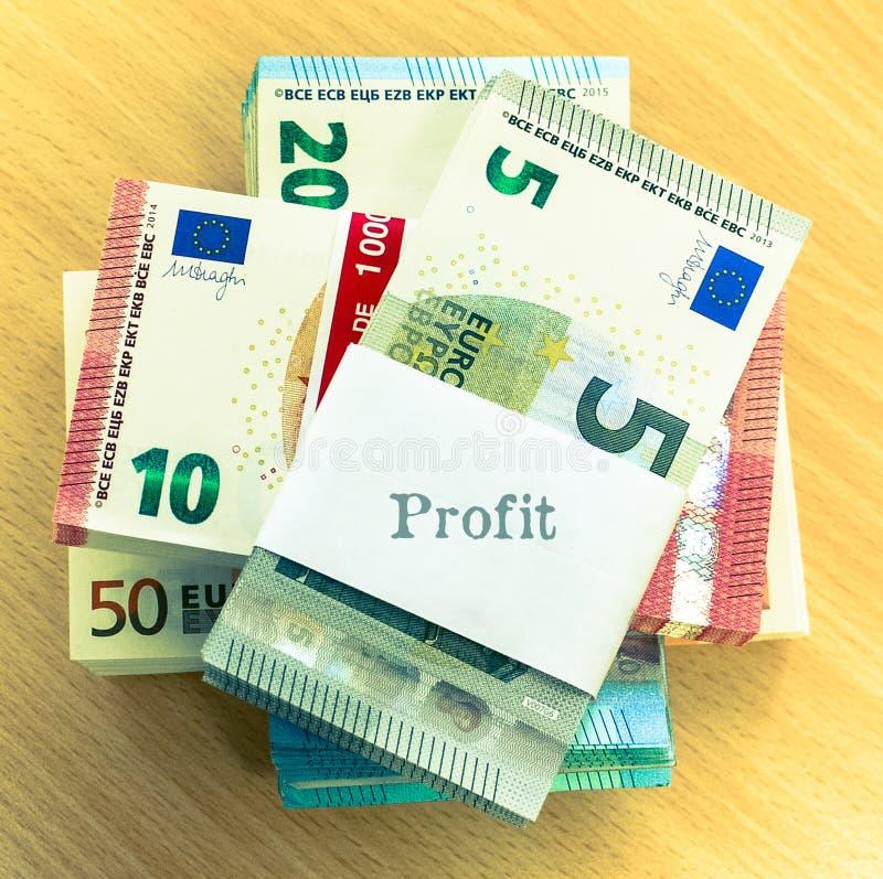 Stapel der Eurorechnungen auf einem Kiefernschreibtisch, beschriftet ` Gewinn ` stockfotos