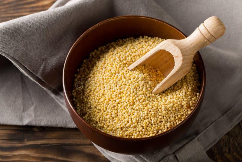 Stapel der goldenen Hirse, ein freier Kornsamen des Glutens, in der hölzernen Schüssel auf grauem Geschirrtuch auf braunem hölzer lizenzfreie stockfotografie