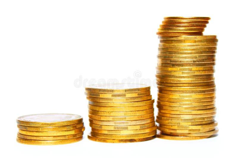 Stapel der goldenen Münzen getrennt auf einem weißen Hintergrund lizenzfreies stockbild