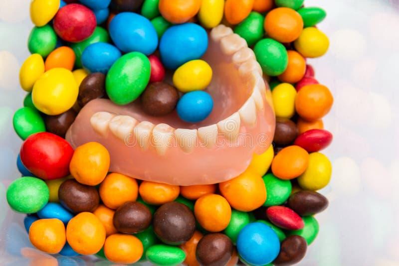 Stapel der Süßigkeit und des zahnmedizinischen prothesis in den Farbbonbonbonbons stockbilder