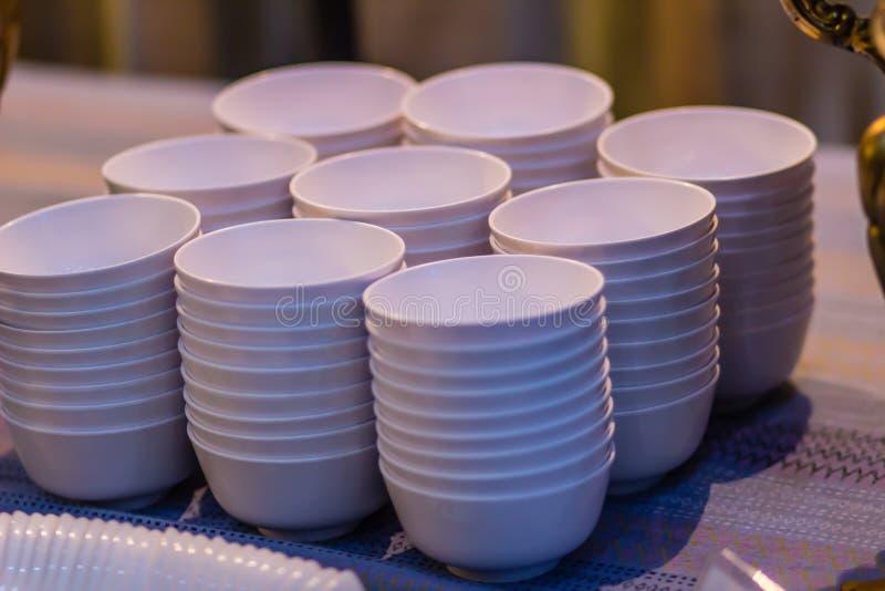 Stapel der sauberen weißen Schüssel auf einer Tabelle für ein Buffet im Restaurant Gesäuberte weiße Suppen- oder Salatschüsseln i stockbild