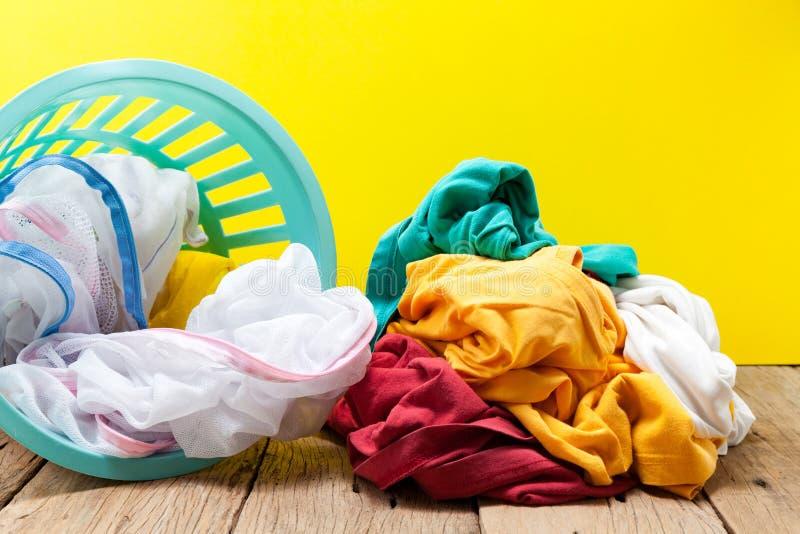 Stapel der Schmutzwäsche in waschendem Korb auf hölzernem, gelbem backgro stockfoto