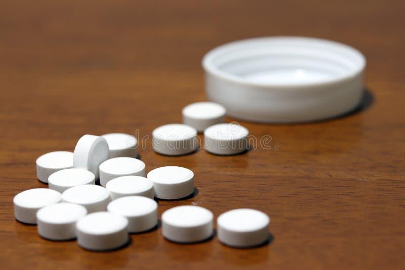 Stapel der weißen runden Medizin auf dem Bretterboden und der weißen Plastikkappe lizenzfreie stockfotografie