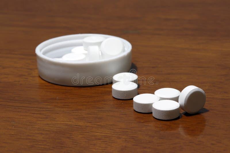 Stapel der weißen runden Medizin auf dem Bretterboden und der weißen Plastikkappe stockfotos